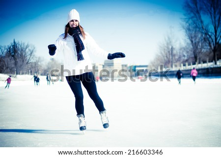 Attractive young woman ice skating during winter - stock photo