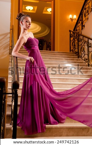 attractive young woman in a beautiful dress sloit on the stairs in the hotel lobby - stock photo