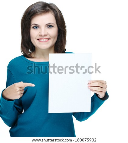 Attractive young woman in a blue shirt. Holds a poster and points on it. Isolated on white background