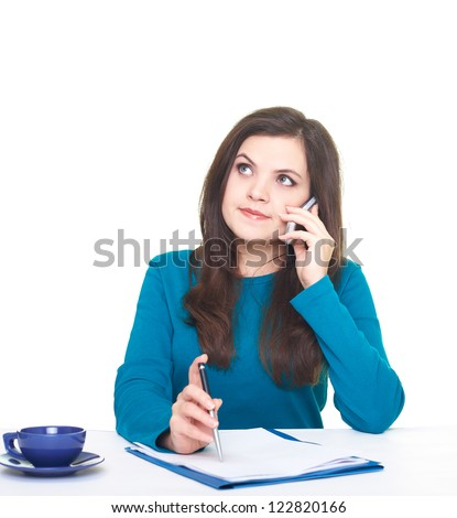 Attractive young woman in a blue shirt sitting at a table and talking on a mobile phone. Looks into the upper-right corner. Isolated on white background - stock photo