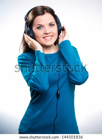 Attractive young woman in a blue shirt. Woman with headphones listening to music. On a white background