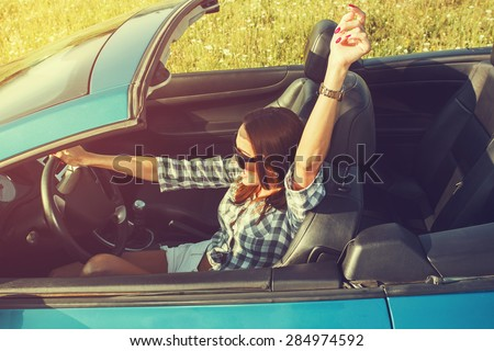 Attractive young woman in a convertible car - stock photo