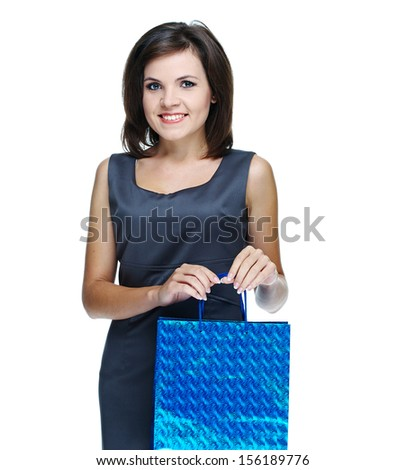 Attractive young woman in a gray business dress. Holds the gift bag. Isolated on white background