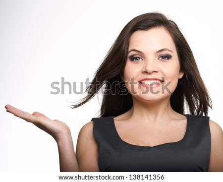 Attractive young woman in a gray business dress. Woman holds an imaginary object in her right hand. On a white background