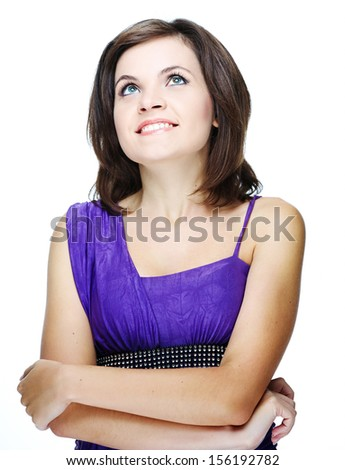 Attractive young woman in a lilac dress. Standing with folded hands. Looking up. Isolated on white background