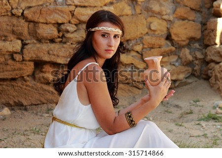 Attractive young woman in a long white gown with beautiful hairstyle holding an amphora in the background of an old stone wall - stock photo
