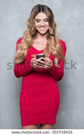 Attractive young woman in a red dress. Woman holds a mobile phone sending a text message - stock photo