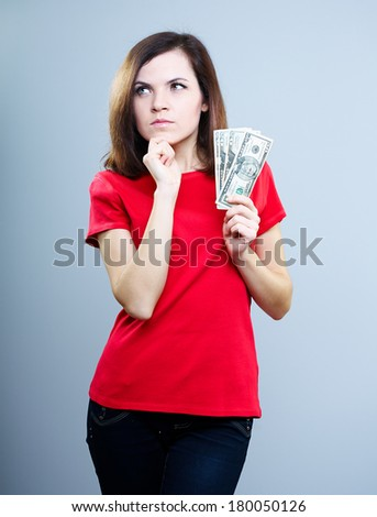 Attractive young woman in a red shirt. Holding dollars and thinks. On a gray background