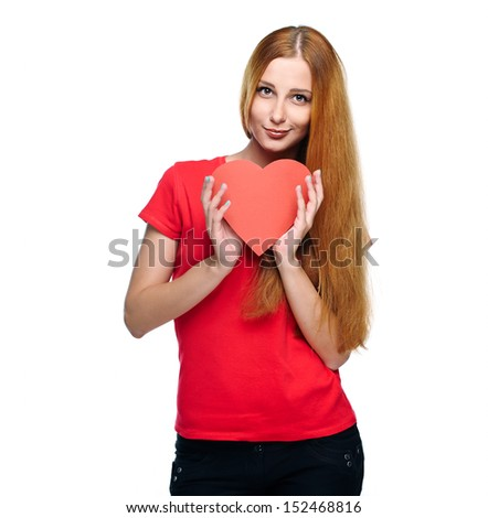 Attractive young woman in a red shirt. Holding red heart. Isolated on white background