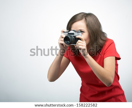 Attractive young woman in a red shirt. Holds the camera. On a gray background - stock photo