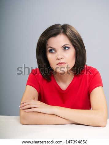 Attractive young woman in a red shirt sitting at the table. Woman thinking and looking to the right. Isolated on a gray background - stock photo