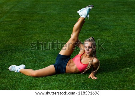 Attractive young woman in a sports suit doing exercises on a green field stadium - stock photo