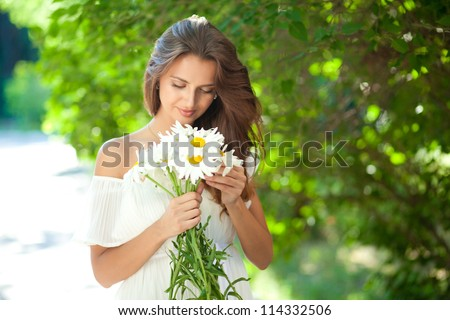 Attractive young woman in a white summer dress holding a bouquet of daisies - stock photo