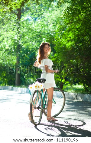 Attractive young woman in a white summer dress standing and holding on old bike