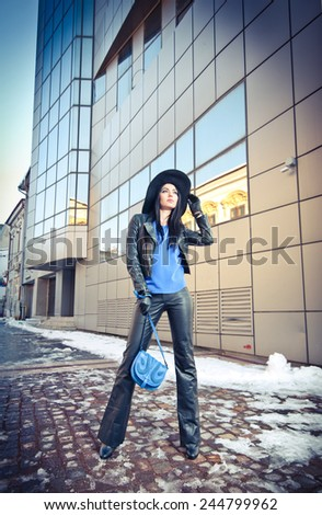Attractive young woman in a winter fashion shot. Beautiful fashionable young girl in black leather with big hat and blue handbag posing in front of modern building, urban scenery. - stock photo