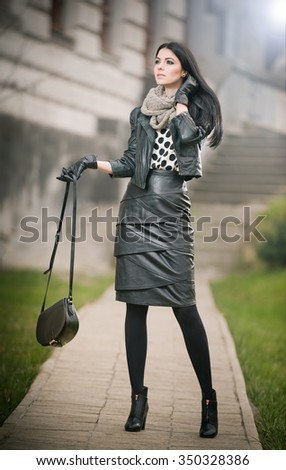 Attractive young woman in a winter fashion shot. Beautiful fashionable young girl in black leather waking on avenue. Elegant long hair brunette with handbag and scarf in urban scenery. - stock photo