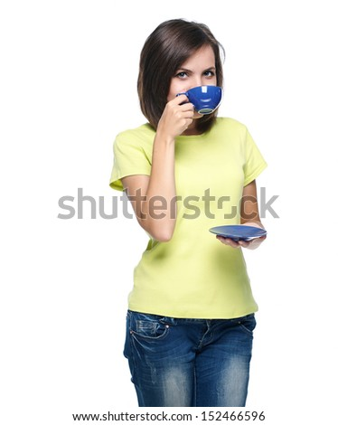 Attractive young woman in a yellow shirt. Drinking from a blue cup. Isolated on white background