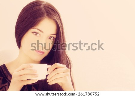 attractive young woman in bed with a cup of coffee - stock photo