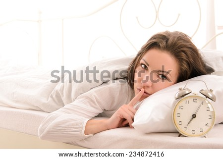 attractive young woman in bed with alarm clock - stock photo