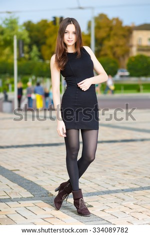Attractive young woman in black dress posing outdoors - stock photo