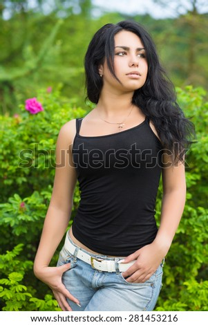 Attractive young woman in black t-shirt posing near the bushes - stock photo