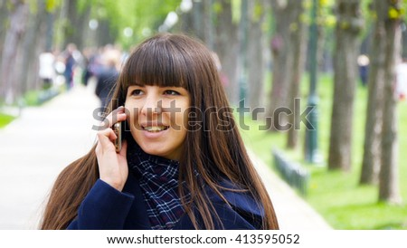 Attractive young woman in blue coat talking on the mobile phone in the alley in the park. Happy girl talking on smartphone, outdoors. Close-up - stock photo