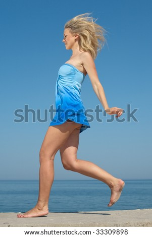 Attractive young woman in blue running on seashore