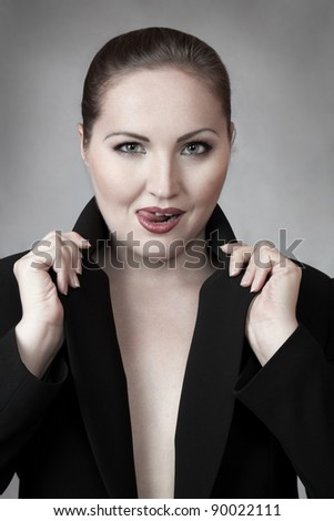 Attractive young woman in business suit with tongue put out - stock photo