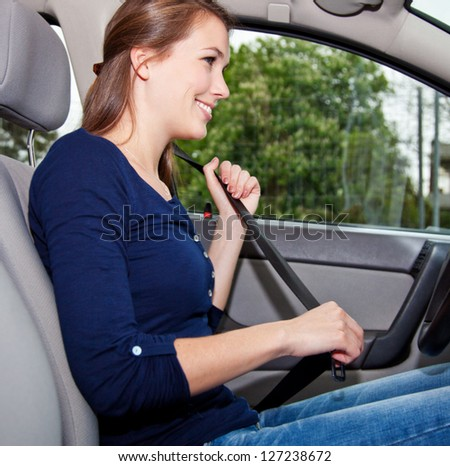 Attractive young woman in car fastens seat belt - stock photo