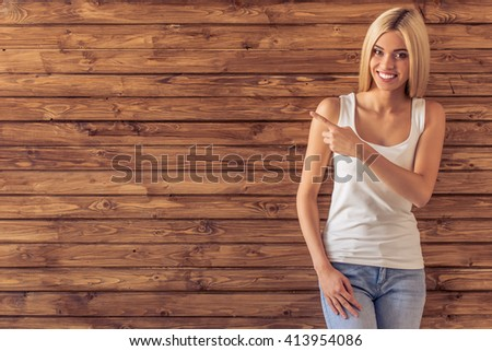 Attractive young woman in casual clothes is pointing, looking at camera and smiling, standing against wooden wall - stock photo