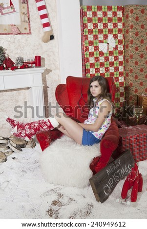 Attractive Young Woman in Casual Clothing Sitting on the Floor Near Christmas Tree - stock photo