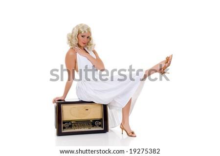 Attractive young woman in classy white dress sitting on retro radio. Studio shot, white background. - stock photo