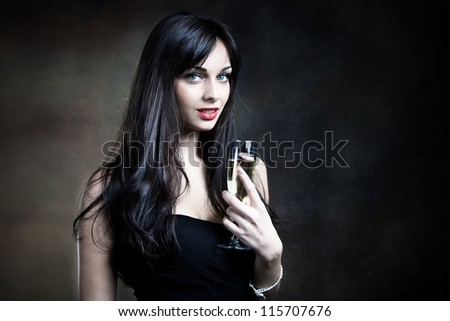 attractive young woman in elegant dress and glass of champagne - stock photo