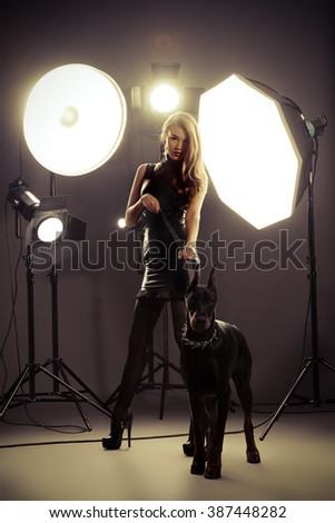 Attractive young woman in fitting leather suit alluring with her beautiful dog at studio in the light flashes. Fashion shot.