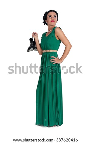 Attractive young woman in green dress with shoes in hand. Isolated over white background - stock photo