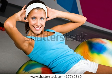 Attractive young woman in health club with pilates ball - stock photo