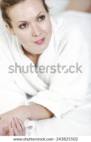 Attractive young woman in her bath robe lying on a bed - stock photo