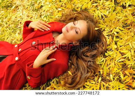 Attractive young woman in red coat lying in autumn leaves, outdoor.  - stock photo