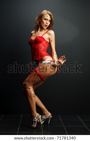 Attractive young woman in red lingerie on a dark background - stock photo
