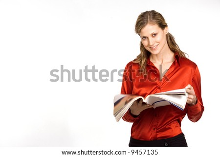 Attractive young woman in red shirt reading magazine - stock photo