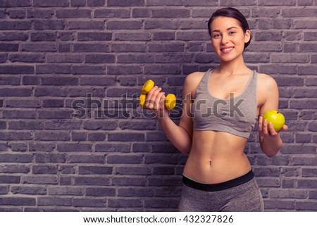 Attractive young woman in sportswear is holding dumbbells and apple, looking at camera and smiling, against brick wall - stock photo