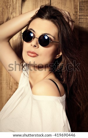Attractive young woman in sunglasses and casual t-shirt stands by a wooden wall.