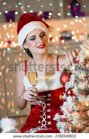Attractive, young woman in the Santa Claus costume holding glass of champagne and looking at Christmas tree. Bokeh background, shallow doff - stock photo