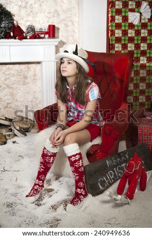 Attractive Young Woman in wearing white man hat  and Casual Clothing Sitting on the Floor Near Christmas Tree - stock photo