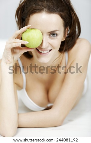 Attractive young woman in white underwear with a fresh apple - stock photo