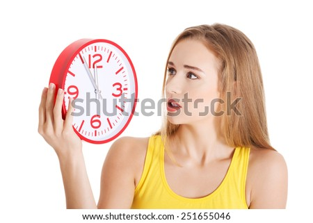 Attractive young woman in yellow top holding a clock. Isolated on white. - stock photo