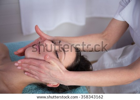 Attractive young woman is getting head massage at spa. She is lying and relaxing. The masseuse is standing and massaging female body carefully - stock photo