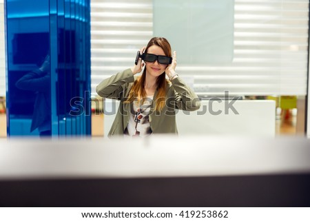 Attractive young woman is looking for a new 3D tv. She is holding 3D glasses and looking at TV. Shallow depth of field. - stock photo