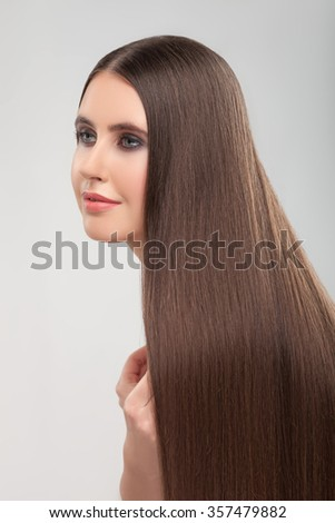 Attractive young woman is standing with long straight smooth hairstyle. She is smiling and looking forward with joy. Isolated on grey background - stock photo