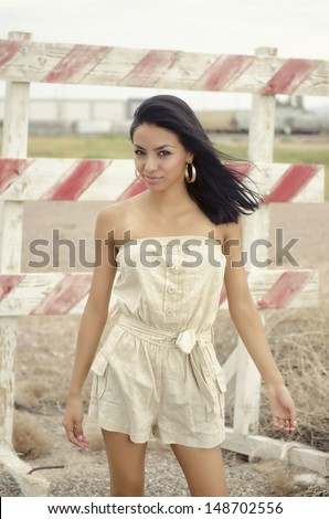 Attractive young woman is stylish romper dress - stock photo
